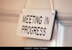 Royalty free photograph of meeting in progress sign hanging on door showing meeting in progress