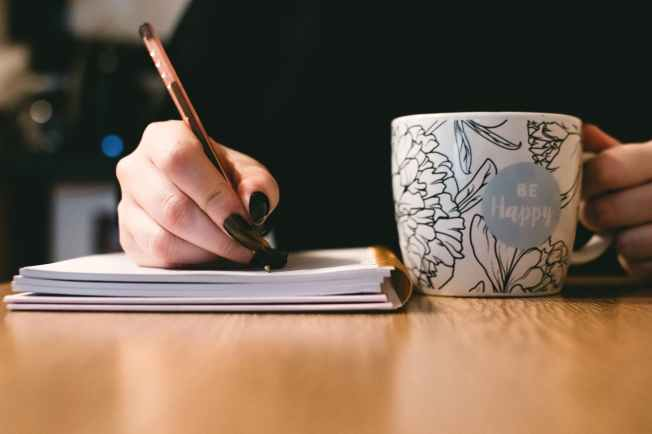 person holding white ceramci be happy painted mug